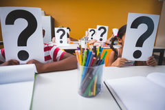 School kids covering their face with question mark sign. In classroom at school Stock Image