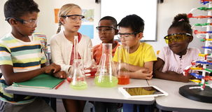 School kids doing chemical experiment in classroom stock video footage