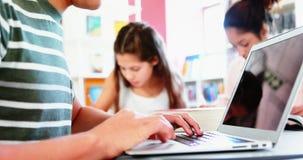 School kids doing homework in library stock video footage