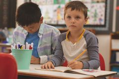 School kids drawing on notebook in classroom. Front view of Caucasian school kids drawing on notebook in classroom at school stock photos