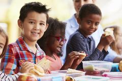 School kids eating packed lunches together at a table stock images