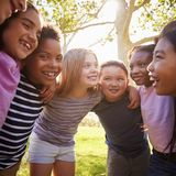 School kids embrace standing in a circle, square format stock images