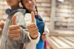 School kids giving thumbs up. Defocused school students, boy and girl, giving thumbs up at camera in library Royalty Free Stock Photography