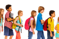 School kids go in line with backpacks profile view. Diverse group of school age kids boys and girls walking in a line wearing backpacks isolated on white profile Stock Photos