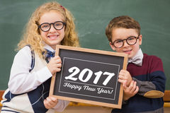 School kids holding chalkboard with new year text Royalty Free Stock Image