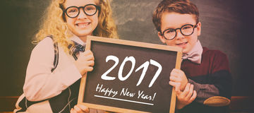 School kids holding chalkboard with new year text Royalty Free Stock Photography