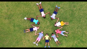 School kids holding hands while lying in circle on grass. At school playground 4k stock video footage