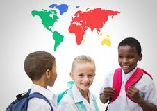 School kids laughing in front of colorful world map. Digital composite of School kids laughing in front of colorful world map Royalty Free Stock Images