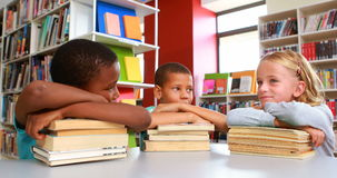 School kids leaning on stack of books in library stock video footage