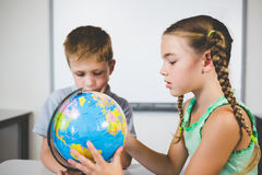 School kids looking at globe in classroom Stock Photography