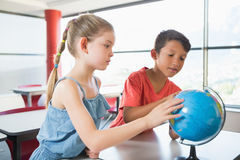 School kids looking at globe in classroom Royalty Free Stock Photos