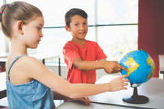 School kids looking at globe in classroom Stock Photo