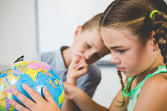 School kids looking at globe in classroom Stock Images
