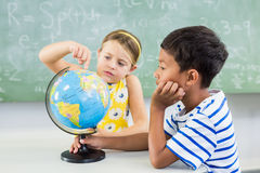 School kids looking at globe in classroom Royalty Free Stock Photo