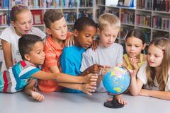School kids looking at globe in library Royalty Free Stock Photography