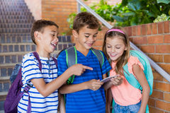 School kids looking at mobile phone Stock Image