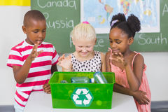 School kids looking recycle logo box in classroom Royalty Free Stock Photos