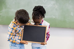 School kids looking at slate in classroom Royalty Free Stock Photo
