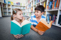 School kids lying on floor and reading a book in library. At school Stock Photos