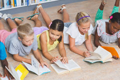 School kids lying on floor reading book in library Royalty Free Stock Photography