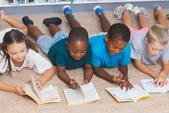 School kids lying on floor reading book in library Stock Photo