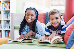 School kids lying on sofa and reading book Stock Images