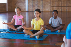School kids meditating during yoga class Stock Photography