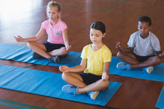 School kids meditating during yoga class Royalty Free Stock Images