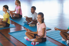 School kids meditating during yoga class. In basketball court at school gym Stock Images