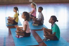 School kids meditating during yoga class. In basketball court at school gym Stock Photos
