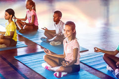 School kids meditating during yoga class. In basketball court at school gym Stock Image