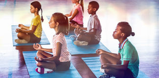 School kids meditating during yoga class. In basketball court at school gym Stock Photo