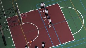 School kids playing basketball at a basketball court Royalty Free Stock Images