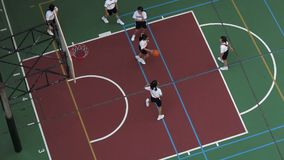 School kids playing basketball at a basketball court stock footage