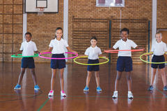 School kids playing with hula hoop in in basketball court Royalty Free Stock Photography