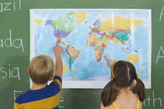 School kids pointing at map in classroom royalty free stock photo
