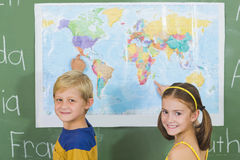 School kids pointing at map in classroom. Portrait of school kids pointing at map in classroom at school stock photo