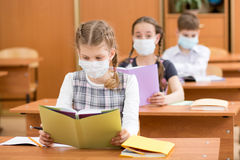 School kids with protection mask against flu virus at lesson. School children with protection mask against flu virus at lesson Stock Images