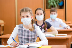 School kids with protection mask against flu virus. Schoolkids with protection mask against flu virus at lesson Stock Photo