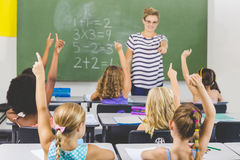 School kids raising hand in classroom. At school Stock Images
