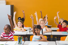 School kids raising hand in classroom. Smiling school kids raising hand in classroom at school Royalty Free Stock Image