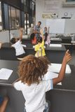 School kids raising hand in classroom at school with teacher in background royalty free stock images