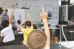 School kids raising hand in classroom at school with teacher in background royalty free stock image