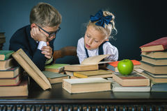 School kids reading a book at library Royalty Free Stock Photos
