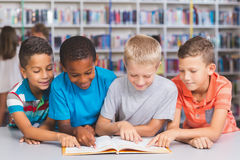 School kids reading book together in library Royalty Free Stock Image