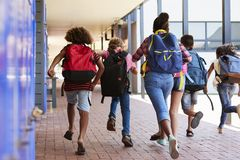 School kids running in elementary school hallway, back view Stock Photography