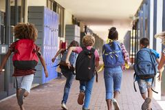 School kids running in elementary school hallway, back view Royalty Free Stock Image