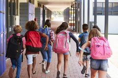 School kids running in elementary school hallway, back view Royalty Free Stock Photos