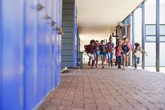 School kids running to camera in elementary school hallway Stock Photos