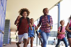 School kids running to camera in school hallway, close up Royalty Free Stock Photos